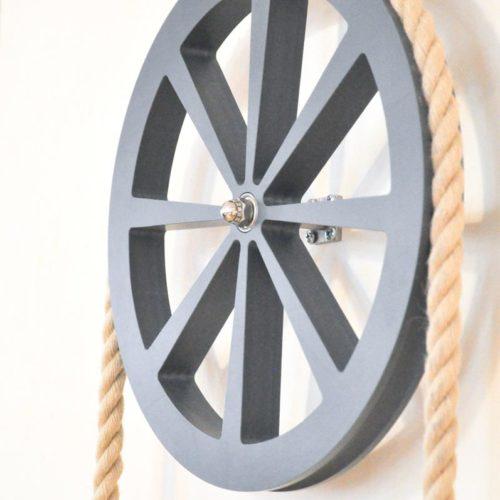 Detail boekenkast Move on Time. Het wiel met het touw.