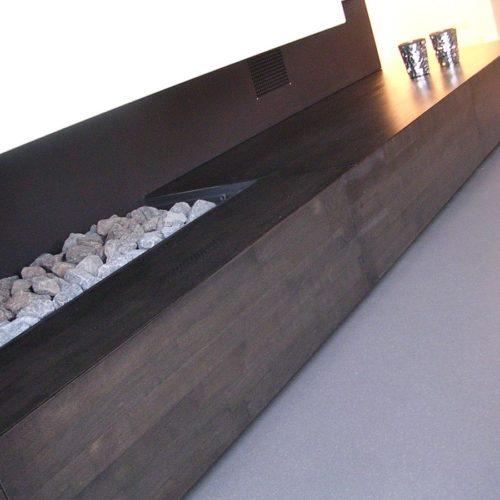 Deze geheel zwevende open haard-wand Daring is voorzien van kleppen voor opbergruimte.