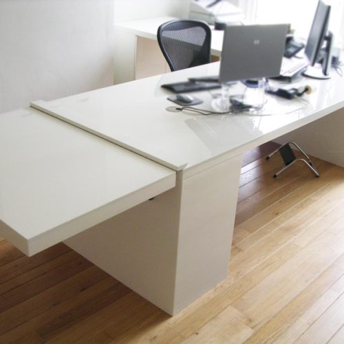 Kantoorruimte 'at home at work'. Modern bureau in hoogglans wit met uitklapblad uitgeklapt