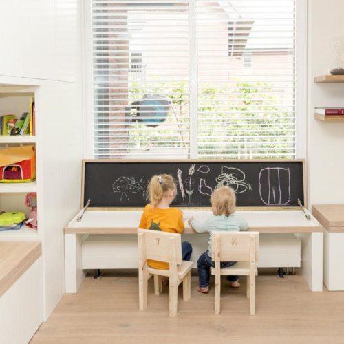 Twee kinderen zitten voor hun krijtbord. Links is de leeshoek te zien.
