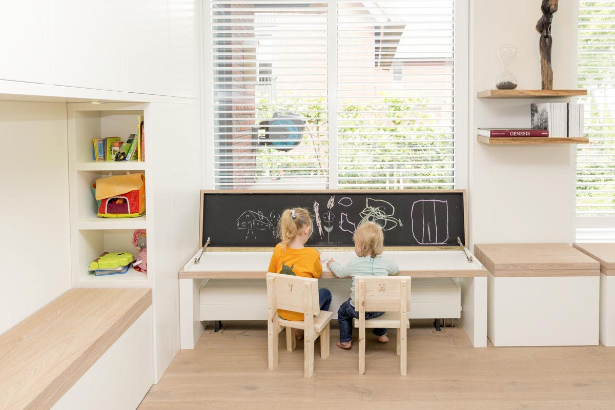 twee kinderen zitten voor hun krijtbord links is de leeshoek te zien