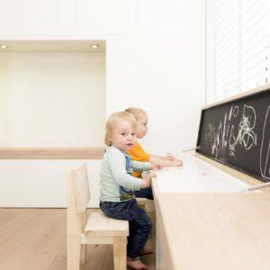 Kinderen zitten voor hun krijtbord in hun speelhoek in de huiskamer.