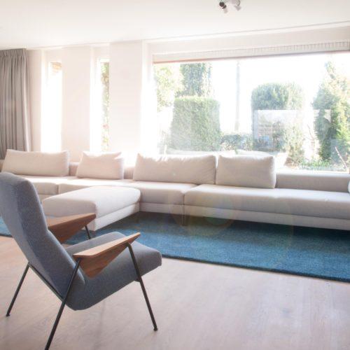 Interieurontwerp met een zeer lange bank in u-vormige huiskamer. Het ingebouwde dressoir geeft een chique effect.