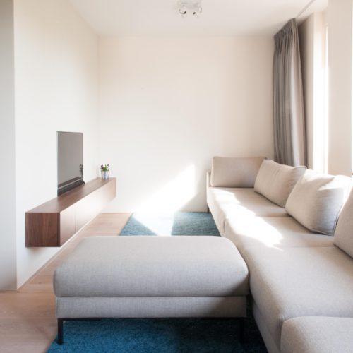 Zij-aanzicht van de witte, zes meter lange bank in deze u-vormige huiskamer en keuken.